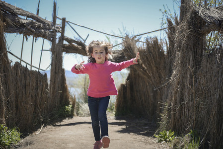 Little girl walking on a path of in a wetland