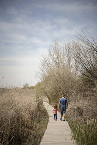 Father and little daughter walking on a path of wooden boards in
