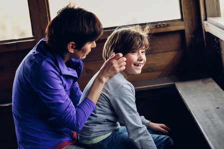 Mother with her seven year old daughter laughing in a cabin in t