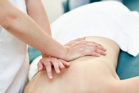 Young woman receiving a back massage by professional therapist