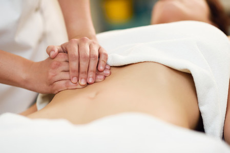 Therapist applying pressure on belly  Hands massaging woman abdo