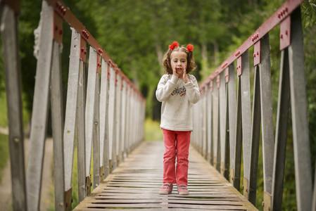Cute little girl having fun in a rural bridge