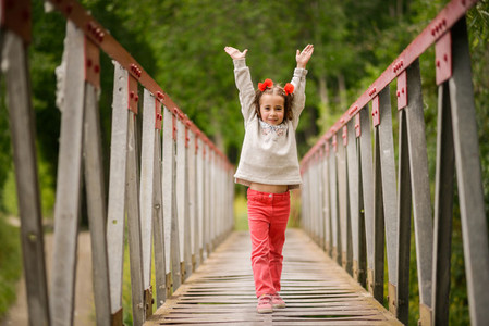 Cute little girl having fun in a rural bridge
