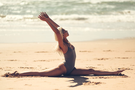 Caucasian blonde woman practicing yoga in the beach