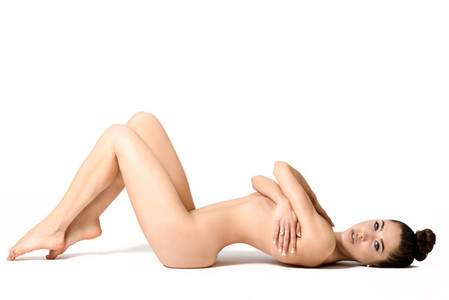 Young fit naked girl with healthy clean skin lying down