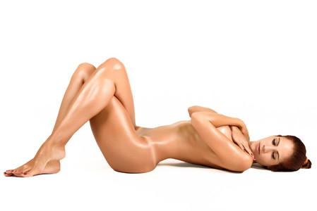 Young naked woman laying on white floor