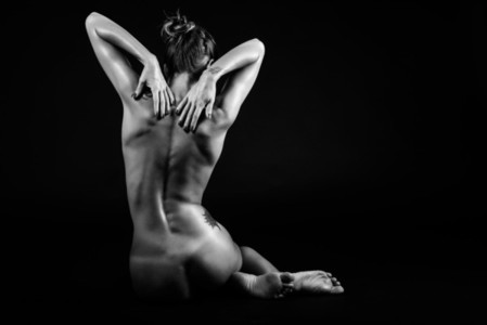 Young naked woman posing on black background