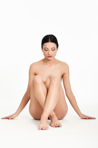 Young naked brunette woman sitting on white floor