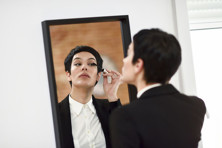Young woman with very short haircut  putting makeup on in front