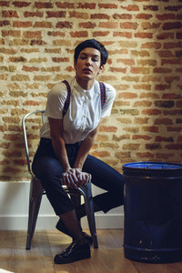 Beautiful young woman model of fashion with very short haircut looking at camera sitting on chair with a brick wall in the background