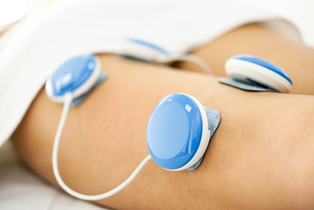 Electro stimulation in physical therapy to a young woman leg
