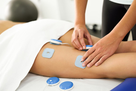 Physiotherapist applying electro stimulation in physical therapy