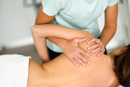 Professional female physiotherapist giving shoulder massage to a