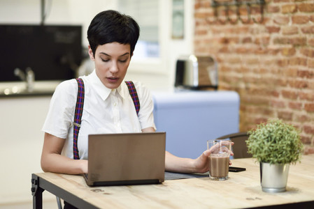 Young woman with very short haircut typing with a laptop at home