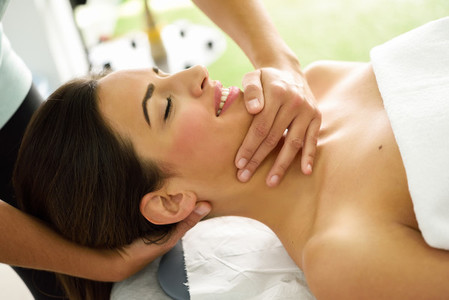Young smiling woman receiving a head massage in a spa center