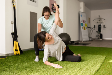 Physiotherapist assisting young caucasian woman with exercise wi