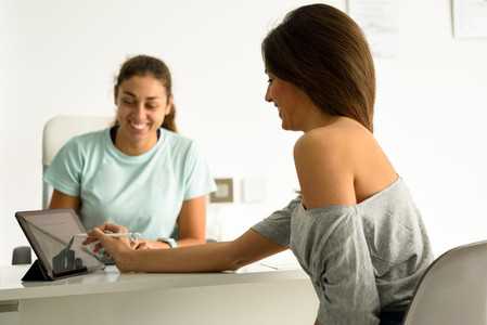 Woman accepting and signing her diagnosis with female physiother