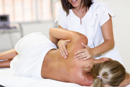 Professional female physiotherapist giving shoulder massage to b