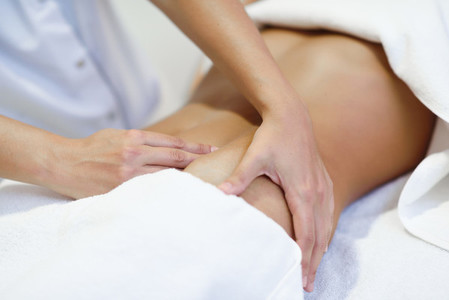 Woman receiving a belly massage at spa salon