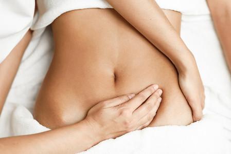 Hands massaging female abdomen Therapist applying pressure on be