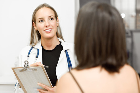 Female doctor explaining diagnosis to her young woman patient