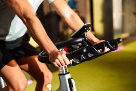 Hands of a man training at a gym doing cyclo indoor