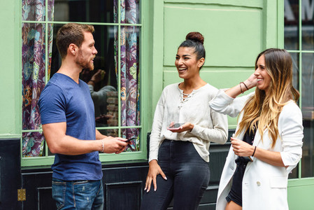 Three multiethnic people friends laughing outdoors