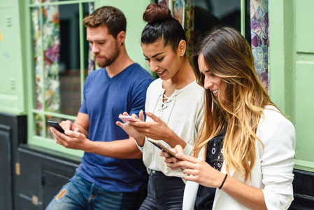Group of three people looking down at smart phone smiling