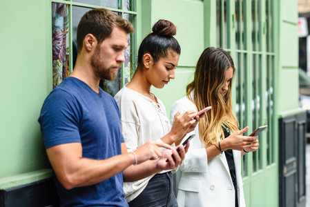 Multiracial group of people looking down at smart phone