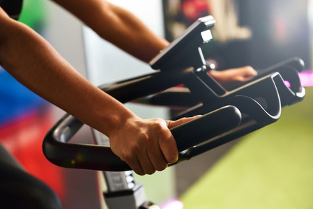Woman at a gym doing spinning or cyclo indoor with smart watch