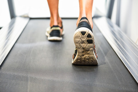 Male muscular feet in sneakers running on the treadmill at the gym
