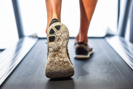 Male muscular feet in sneakers running on the treadmill at the g