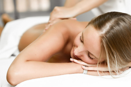 Young blonde woman having massage in the spa salon