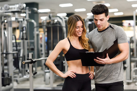 Personal trainer and client looking at her progress at the gym
