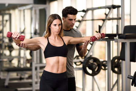 Personal trainer helping a young woman lift weights