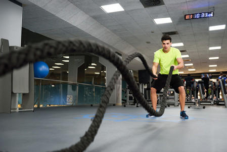 Man with battle ropes exercise in the fitness gym