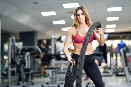 Woman with battle ropes exercise in the fitness gym