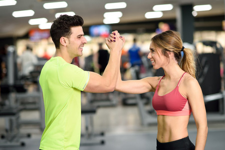 Smiling young man and woman doing high five in gym