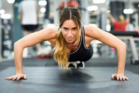 Young beautiful woman doin pushups in the gym