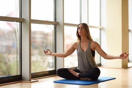 Young beautiful woman meditating in the lotus position in gym