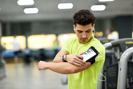 Young man using smartphone standing in the gym