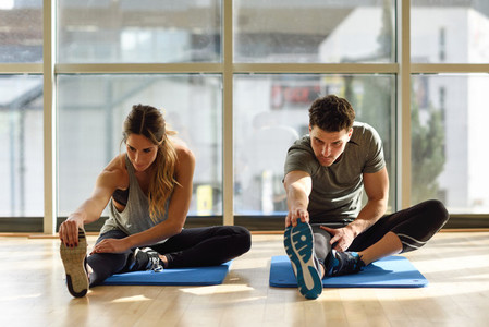 Two people streching their legs in gym