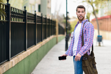 Young bearded man surprised in urban background  Lifestyle conce