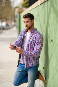 Attractive young man standing in urban background Lifestyle con