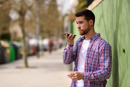 Young man recording voice note in his smart phone in urban backg