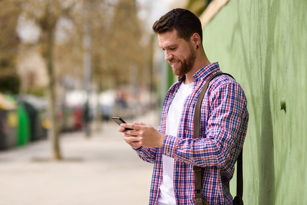Smiling young man looking his smart phone in urban background L