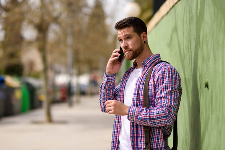 Young man talking with his smart phone in urban background  Life