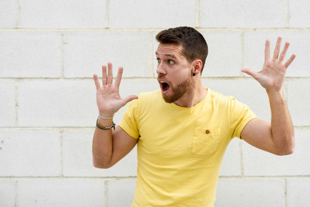 Funny young man on brick wall with open hands looking at leftsid