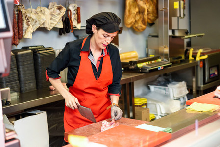 Female butcher cutting meat at counter in butchery