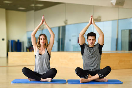 Young woman and man practicing yoga indoors